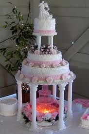 Three tier white buttercream wedding cake hoisted up on pillars to cater for a glorious water fountain. Decorated with pink flowers and pink decorative ribbon around each tier. ((( This was my wedding cake! Elegant Wedding Cakes, Beautiful Wedding Cakes, Wedding Cake Designs, Wedding Cake Toppers, Beautiful Cakes, Fountain Cake, Fountain Wedding Cakes, Fountain Ideas, White Buttercream