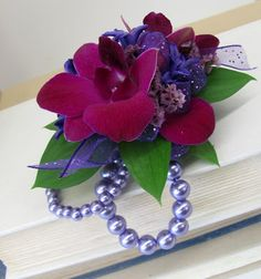FREE CORSAGE TUTORIALS http://www.wedding-flowers-and-reception-ideas.com/how-to-make-a-corsage.html   Fushia dendrobium blooms are on a pearled wristlet bracelet and accented with pink statice and purple sparkle ribbon.  Learn how to make your own corsages and boutonnieres using professional florist supplies and techniques.