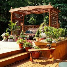 """Backyard Landscaping Ideas Garden Structure Lovely Lattice Garden Structure: A swing surrounded by a lattice arbor says """"summer relaxation"""" like nothing else. The airy structure visually anchors the deck. Lattice on top of an outdoor garden structure provides a great place to hang baskets of shade-loving plants, such as the ferns shown here."""