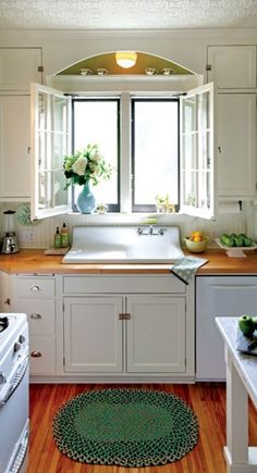 Salvaged casement windows, butcher-block countertops, and an antique sink returned light to this once-dark kitchen in a 1905 Colonial Reviva...