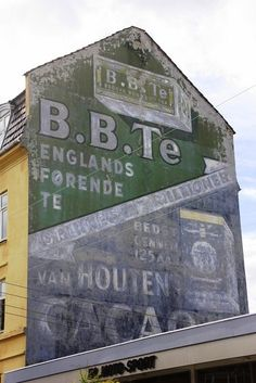 Two fading painted signs advertising B.B.Te and Van Houten Cacao