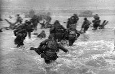 """""""Ainda era muito cedo e bastante escuro para conseguir boas fotos, mas a água e o céu cinzas fizeram daqueles homens, que se esquivam por entre o design surrealista antiinvasão montado por especialistas de Hitler, uma imagem muito forte."""" - Robert Capa"""