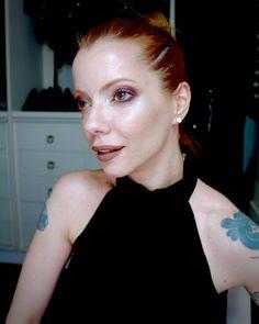Julia Petit olhos esfumados com sombra vermelha e iluminador dourado na pele.