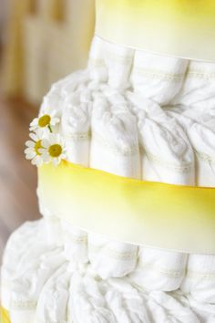 Sweet as Lemonade Diaper Cake. 100 HUGGIES® Pure & Natural Diapers, 100 rubber bands, wide yellow ribbon and lemon toppers. Create a sign and add yellow flower accents.