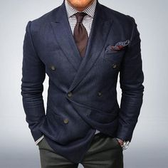 Pairing a navy double breasted blazer and olive green suit pants will create a powerful and confident silhouette.   Shop this look on Lookastic: https://lookastic.com/men/looks/double-breasted-blazer-dress-shirt-dress-pants/22870   — White Check Dress Shirt  — Dark Brown Tie  — Navy Paisley Pocket Square  — Navy Double Breasted Blazer  — Olive Dress Pants  — Brown Leather Watch