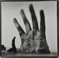 Keith Carter uses fragmentation to a small degree by placing a dark figure to imply the thumb of the large hand. This is an excellent representation of metaphor as well.