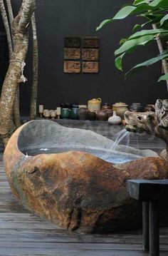 Outdoor carved natural stone bathtub....not sure about having the water come out of that dragons mouth though