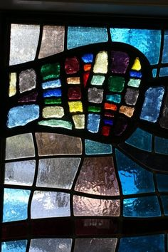 """This design was created as an art piece in a wall, with the idea in mind to use a combination of the Dalle-de-verre technique and traditional leaded glass glass. This juxtaposition contrasts the thick chunky glass with the delicate lines of leaded areas. All glass in the window is from Blenko Glass Company, Milton, WVa. 57""""w x 32""""h 2009"""
