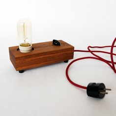 Lamp 'Turn'.  This lamp is handcrafted in small series of oiled teak wood. The bakelite knob controls the dimmer and switches the lamp on/off.