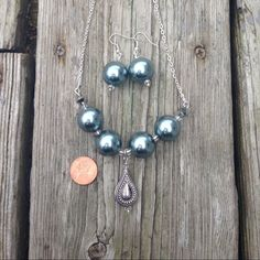 Necklace and earring set. 22 inch Silvertone necklace.   Large, smoky, grey pearls shine in this appealing necklace. Earrings are included with the set. Jewelry Necklaces