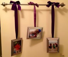 Hang a curtain rod on the wall in your entry way, hang photos with ribbon.
