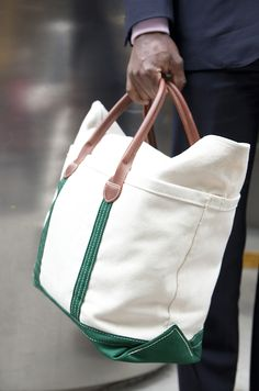 A casual alternative to a briefcase, this canvas tote with green accents and leather handles is colorful but classy. The owner of the hand holding it, Daniel Balroza, works in Private Equity.