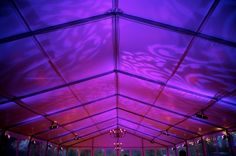 Lighting projections on the ceiling of a Clearspan tent transform the space from day to night. Jen Kroll Photography. A Day in May Events. Special Events Rental.