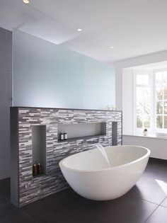 free standing bath by Ashton and Bentley compliments the feature wall. The wall mounted bath filler provides a tranquil flow of water in this relaxing spa bathroom. Bathroom design by David Aspinall .