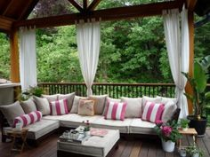 Porch with large cushioned bench and curtains.