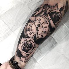Tatuagem feita por Ag Tattoo de São Paulo.    Relógio com flores em preto e cinza no braço.