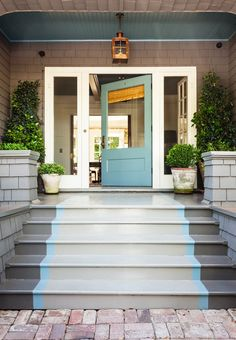The door color, Benjamin Moore'sStratton Blue, is continued into the foyer. A light from Bevolo casts a warm glow on the porch when night falls.