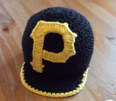 """Choose colours and initial letter for this adorable crochet baseball cap for a baby or big kid! Perfect for that first baseball game, photo-shoot or to celebrate the birthday boy or girl. Fully customizable to match your baby's outfit or your favorite team.  Pictures show """"Pittsburgh Pirates"""" in black; and blue and back show an special order with in"""