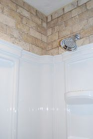 Tile above the shower insert. If you have to live with an insert, might as well make the best of it.