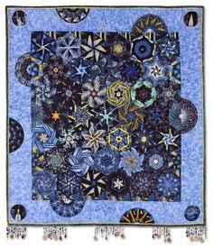 """New York City Lights quilt by Ellen Yamaguchi, Empire Quilters Guild (New York).  Best Use of Beads and/or Embellishments • Viewer's Choice. Artist statement:  """"Kaleidoscope New York City skyline fabric embellished with as many beads, charms and coins I could find."""""""