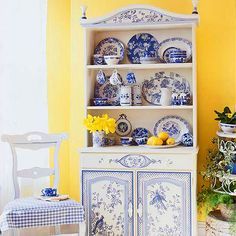 Whimsical & beautiful too. The blue & white are arranged well in the darling cupboard & the yellow wall makes it really pop. Traditional Home