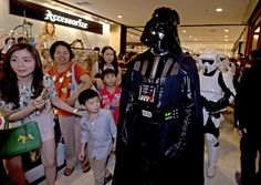 Thailand: A fan dressed as Darth Vader walks in a Bangkok shopping mall to raise funds for an orphanage charity.