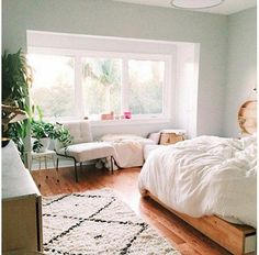 """Blogger It Girl: @designlovefest -- We're digging the all-white bedding and blonde-wood bed frame and wall decor allow for her grounding pieces—a Moroccan rug, a marble-top console, and lots of plant friends—to truly shine. Shop the pieces you need to get the look and see more bedroom interior design inspiration in """"9 Inspiring Instagram Bedroom Ideas to Steal"""" on the One Kings Lane Style Guide!"""
