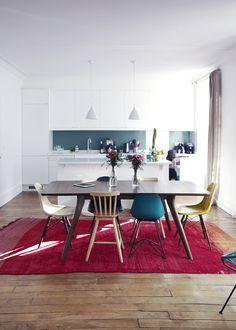 Dans la salle à manger, table en bois Alinéa, tapis Caravane, aux extrémités de la table fauteuils des Eames, chaise haute en bois Ikea