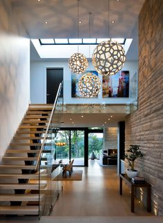 Two story foyer, geometric orb pendant lighting, wood stairs, glass railing, stone wall | Claudia Leccacorvi