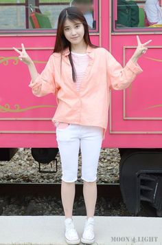 IU wears a pink and white striped top with a coral blouse and white knee shorts and optical white converse high tops