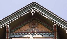Texture. Half-circle butts, painted a warm orange, contribute an extra layer of texture to a shingled gable trimmed in scroll-sawn ornaments.