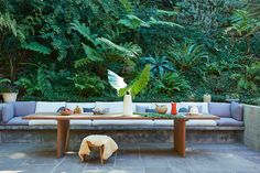The fern-covered hillside makes a lush backdrop for the outdoor dining area, furnished with low-slung, built-in seating and an architectural table.