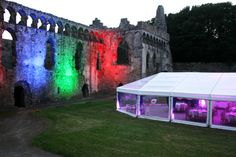 Exterior colour wash can be used to illuminate outside the wedding marquee, buildings and trees, in this case the Bishop's Palace, Pembrokeshire. Installed by www.24carrotevents.co.uk