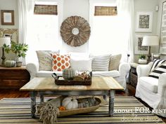 """When temperatures start to drop, Bre of Rooms for Rent layers her living room for what she calls """"fall nesting."""" The essentials? Cozy throws, orange and black accent pillows, pumpkins of varying colors and sizes, and vases filled with mini pinecones."""