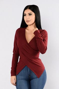 - Available in Rust, Black, Olive, Burgundy, and Ivory - Ribbed Knit Top - Long Sleeve - V- Surplus Neckline - Asymmetrical Hem - Made in USA - 33% Rayon 53% Polyester 4% Spandex