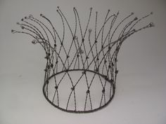 """Black steel wire and 4mm crystals, twisted and woven. About 5"""" diameter."""