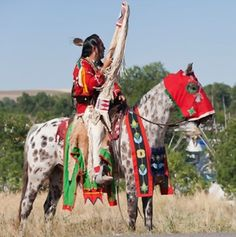 A traditionally dressed Crow Indian man rides an appaloosa horse during the parade, at the annual Indian Crow Fair, at Crow Agency, near Billings, Montana, USA, August 2011