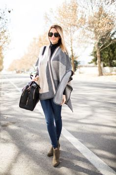 An oversized poncho is essentially a must-have this season. Emily Jackson shows us how to wear the trend, rocking a statement grey number with jeans and pale brown boots.