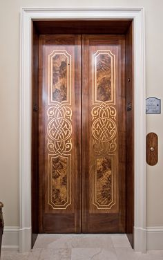 Painted wood grain with gold leaf stencil created by Glenn Williams Finishes on stainless steel elevator doors.