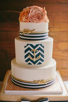 Beautiful 3 tier cake decorated with a cluster of flowers topper with blue & white striped ribbon and gold knots & anchor - DIY Maine wedding | photo by Emily Delamater | 100 Layer Cake
