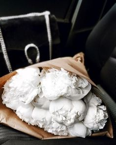 White peonies in brown paper.