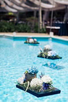 Backyard wedding reception decor idea - floating blue + white floral arrangements in the pool {Michele Ashley Photography}