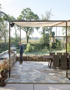 an outdoor dining area is shaded by a mesh canopy suspended by old drilling pipes.   Photo by  Matthew Williams