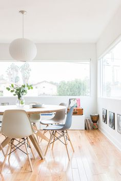 Avid music fans, the breakfast nook is decorated with records, which the couple used at their wedding for guest sign-in. // dining room goals. Large round table, coloured Eames chair, lots of natural light.