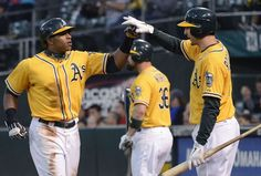 Yoenis Cespedes #52 of the Oakland Athletics is congratulated by Adam Rosales #17 after Cespedes scored on a Josh Donaldson #20 (not pictured) RBI double in the second inning against the Minnesota Twins at O.co Coliseum on August 20, 2012