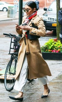 Vanessa Hudgens wears a camel trench coat, white pants, ballet flats, round sunglasses, and a colorful scarf