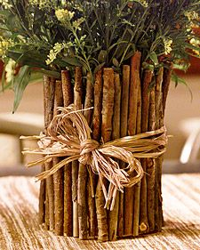 Twig Vase - It's simple to make: Wrap a can with brown paper (or paint it to mask the surface), and cover it with small, straight sticks, gluing them in place (or securing them with a rubber band). Tied with a length of raffia, it makes a charming holder for garden flowers or a rustic desk organizer.