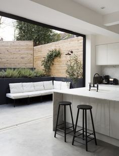 Black bi-folding doors with polished light grey concert floors. Modern horizontal lattice fence.