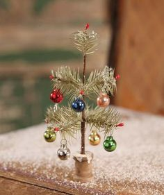 Create an Old Fashioned Christmas atmosphere with this antiqued Tiny Feather Tree on spool base. Aged feather tree with multi-color ornaments . Silver Christmas Decorations, Vintage Christmas Ornaments, Rustic Christmas, Christmas Holidays, Christmas Wreaths, Christmas Bulbs, Old Fashion Christmas Tree, Tiny Christmas Trees, Christmas Villages