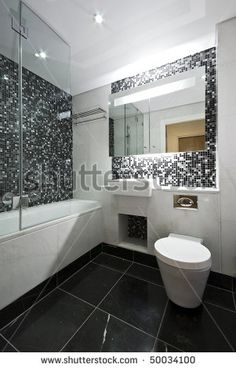 stock photo : Contemporary en-suite bathroom in black and white with white ceramic bath tub, wash basin and toilet with mosaic tiled walls and marble fragments
